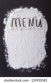 """Handwritten inscription """"Menu"""" is made with flour on the dark surface of the kitchen"""