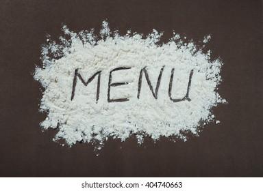 """Handwritten inscription """"menu"""" made with flour"""