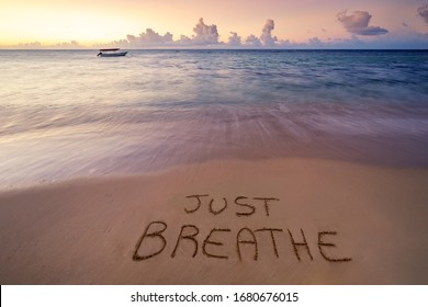 Handwritten Just breathe on sandy beach at sunset,relax and summer concept,Dominican republic beach.