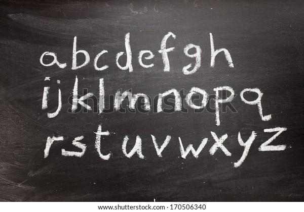 Handwritten letters of the alphabet written on a blackboard
