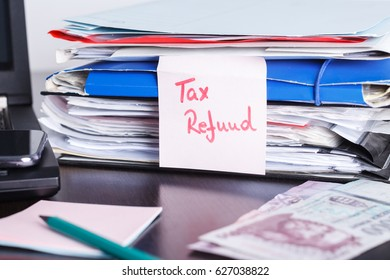 Handwritten note with tax return, refund text, forms and papers, notebook and laptop with mobile phone, cash on the table