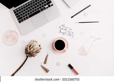 "Handwritten quote ""There is beauty in simplicity"" on paper, female fashion accessories, laptop and protea flower. Still life fashion artistic concept. Flat lay, top view."