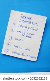 Handwritten Shopping List for Food Bank Items on a Blue Background