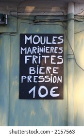 handwritten sign for moules frites at a restaurant in southern france