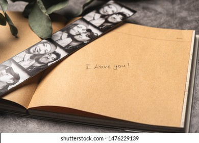 "Handwritten text in notepad ""I love you"". Photo booth strip with the photos of a young couple. Close-up, copy space. Concept of declaration of love and happy memories."