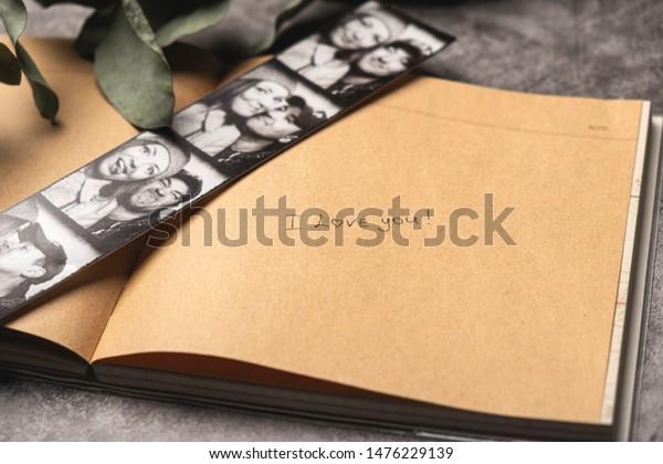 メモ帳の手書きのテキスト「愛してる」。 若い夫婦の写真が入った写真立て。接写スペース。愛と幸せな思い出の宣言のコンセプト。