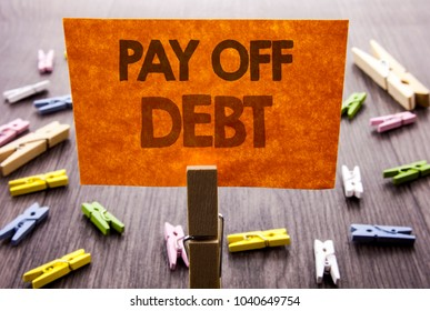 Handwritten text sign showing Pay Off Debt. Business concept for Reminder To Paying Owed Financial Credit Loan Bills written sticky Note the wooden background.