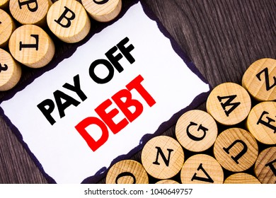 Handwritten text sign showing Pay Off Debt. Business concept for Reminder To Paying Owed Financial Credit Loan Bills written  White Sticky Note the wooden background with letters.