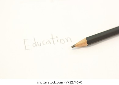Handwritten the word â??educationâ? on white paper near black pencil