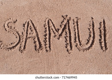 "Handwritten word ""SAMUI"" on brown sand on the beach in sunny day"
