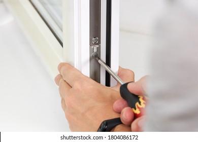 handyman adjusting white pvc plastic window indoors. worker using screwdriver to repair upvc window. homework maintenance.