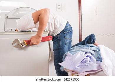 Handyman with big spanner installing washing machine