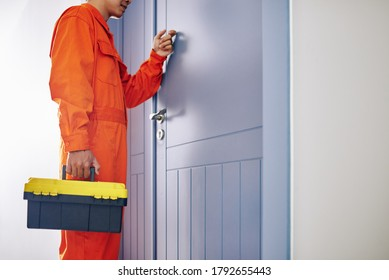 Handyman in bright orange uniform holding toolbox knocking on door of client