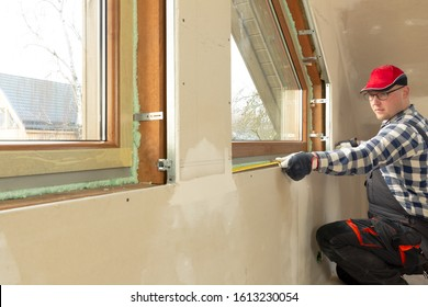 Handyman, construction man installing PVC window in a new insulated and filled dry wall attic.