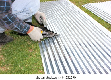 Handyman contractor cutting corrugated iron for roofing repairs