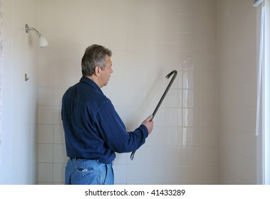 Handyman with a crowbar against bathroom wall
