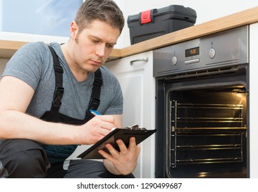 Handyman doing inspection of domestic oven in the kitchen.