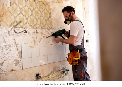 Handyman drilling a wall wearing protective gear and breathing respiration mask
