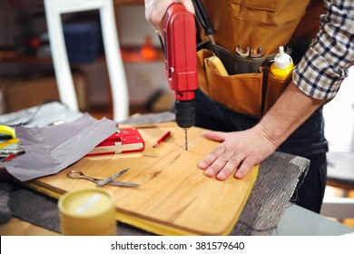 Handyman drilling wooden board in workshop