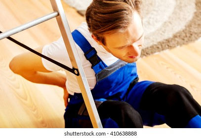 Handyman fell from a ladder and sitting on the floor with backache