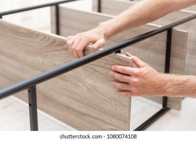 Handyman folds a bookcase. The man is fixing the shelf on the bookshelf.
