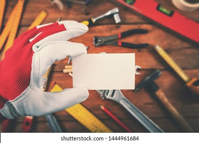 handyman and home repair services - hand holding blank business card over the work tools