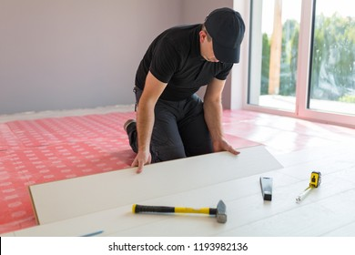 Handyman installing new laminated wooden floor