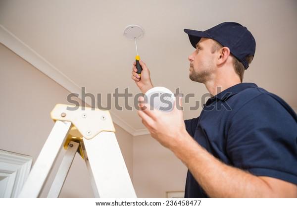 Handyman, der einen Rauchmelder mit Schraubenzieher an der Decke installiert