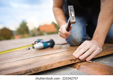 Handyman installing wooden flooring in patio, working with hammer
