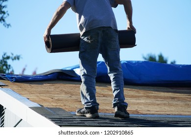 handyman moving waterproof roll when repairing roof