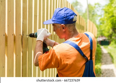 Handyman outdoors works with cordless screwdriver, mounting wooden fence