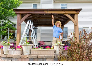 Handyman painting a newly installed wooden gazebo on a patio in front of a house stretching up to paint the underside of the beam viewed over flowers on the patio wall
