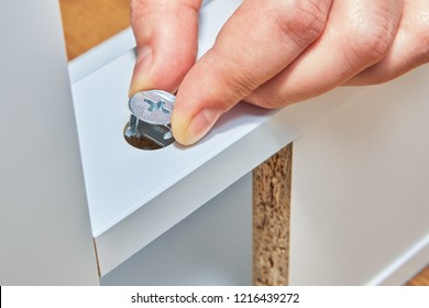 Handyman puts a cam lock nut in the leg of a white wooden table made of particle board, service of putting together ones newly purchased furniture.