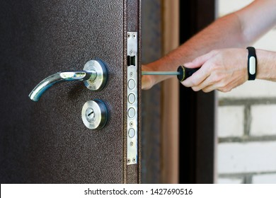 Handyman repair the door lock in metal entrance door, Man fixing lock with screwdriver, Close-up of repairing door, professional locksmith installing new deadbolt lock on house