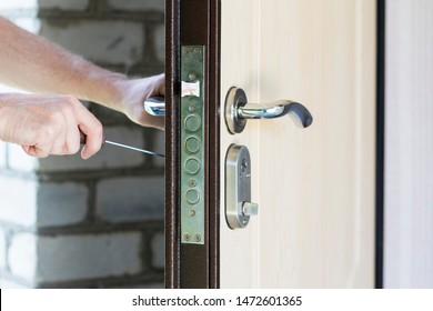 Handyman repair door lock in metal entrance door, Man fixing lock with screwdriver, closeup of repairing door in house.