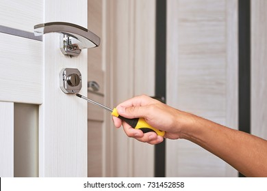 handyman repair the door lock in the room, Man fixing lock with screwdriver, Close-up of repairing door, professional locksmith installing or repairing a new deadbolt lock on a house