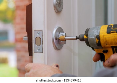 handyman repair the door lock in worker's hands installing new door locker