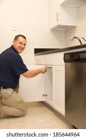 Handyman repairs kitchen cabinet door