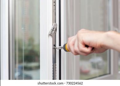 Handyman repairs plastic window with screwdriver.