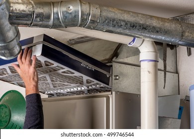 Handyman replaces a furnace filter with a clean one