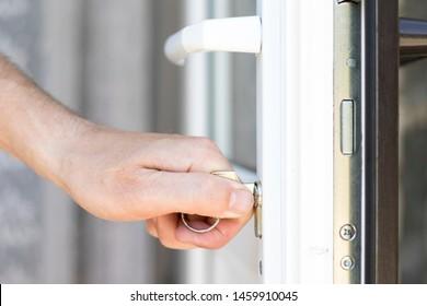 Handyman pone la cerradura en la puerta y abre la puerta.