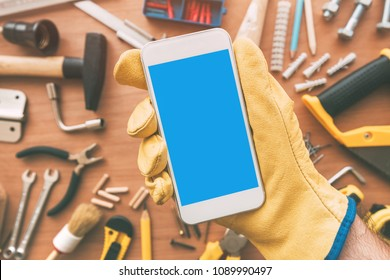 Handyman smart phone app over desk with tools. Repairman holding telephone in hand. Copy space for text, top view