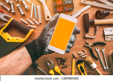 Handyman smartphone app with blank screen. Repairman holding telephone in hand. Copy space for text or maintenance work mobile phone application or business service, top view