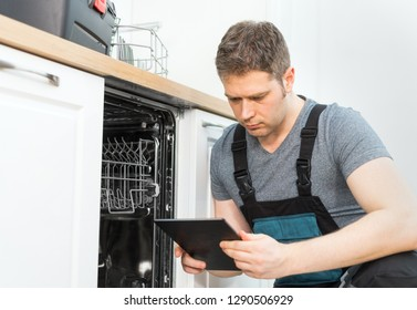 Handyman with tablet pc repairing domestic dishwasher in the kitchen.