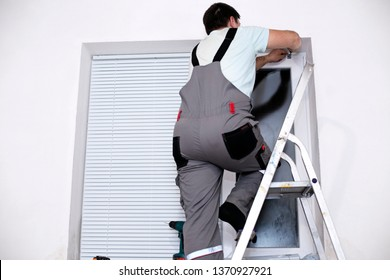 A handyman in a uniform installing new window blinds in the residential or business apartment. Worker providing blind curtain mounting. Professional service - home repair and renovation works