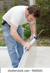 Handyman using a caulking gun to caulk a home improvement project.