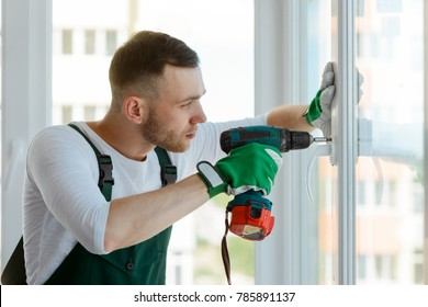 Handyman using a cordless screwdriver to install a window handle. Qualified worker services, home repair and renovation.