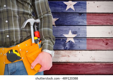 Handyman wearing tool belt against composite image of usa national flag
