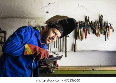 Handyman welding steel in his garage with helmet and safety gloves
