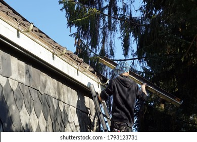 A handyman working and fixing a house rood